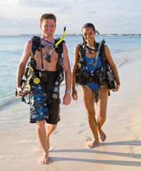 two divers walking on the beach
